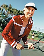 Older woman standing on tennis court with a racket ready.