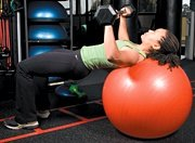 Chelsea Cooper performing stability ball barbell press.