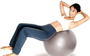 Woman does situps on excercise ball.