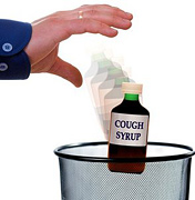 A Hand throwing a bottle of cough syrup into garbage can. - Copyright – Stock Photo / Register Mark