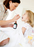 A mother giving her sick little girl some cough syrup.