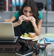 Woman eating at her work desk.