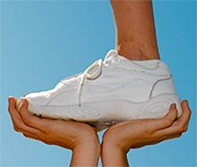 A person standing one-footed on the hands of another person. - Copyright – Stock Photo / Register Mark