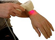 Therapist using low-level laser therapy on his wrist. - Copyright – Stock Photo / Register Mark