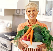 Woman holding large bowl of vegetables.