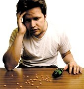 Man with a headache sitting at table with pain pills scattered over its surface. - Copyright – Stock Photo / Register Mark