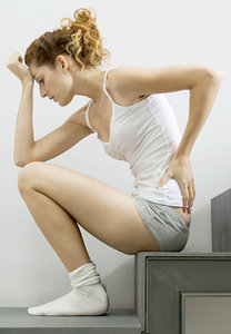Young woman suffering from low back pain. - Copyright – Stock Photo / Register Mark