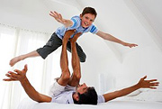 A father using his feet to suspend his young son in the air.