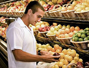 Man examines an apple for purchase. - Copyright – Stock Photo / Register Mark