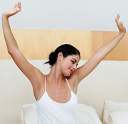 Young woman stretching her arms in bed. - Copyright – Stock Photo / Register Mark