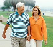 An elderly couple walking near beach.