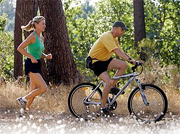 A woman jogging behind a man who is mountain biking.