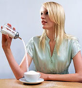 Woman overfilling a coffee cup with sugar.