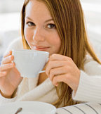 Young woman dringing a cup of hot herbal tea. - Copyright – Stock Photo / Register Mark