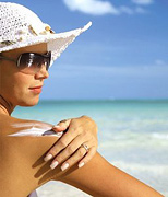 Woman applying sunscreen to her shoulder. - Copyright – Stock Photo / Register Mark