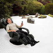 Man sitting in massage chair on zen sand garden.